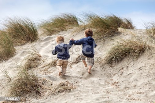 Two brothers holding hands climb a hill at the beach.