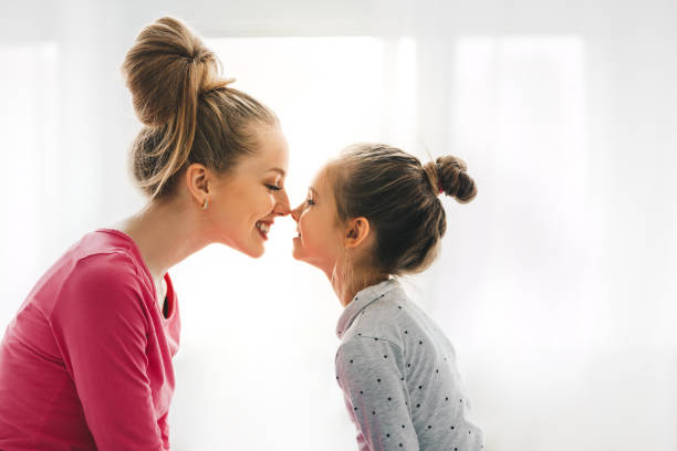 togetherness concept. mom and daughter playing and kissing, loving family - mother imagens e fotografias de stock