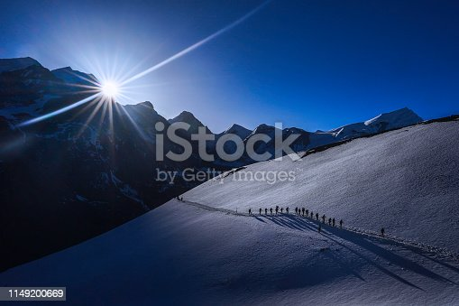 Togetherness concept: Silhoutte a group of hikers with sun at the background during an expedition to Thorong-la Pass via Annapurna Circuit