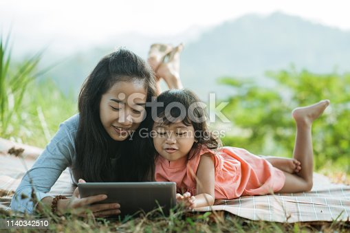 togetherness of women and his daughter enjoy nature lay down watching digital tablet