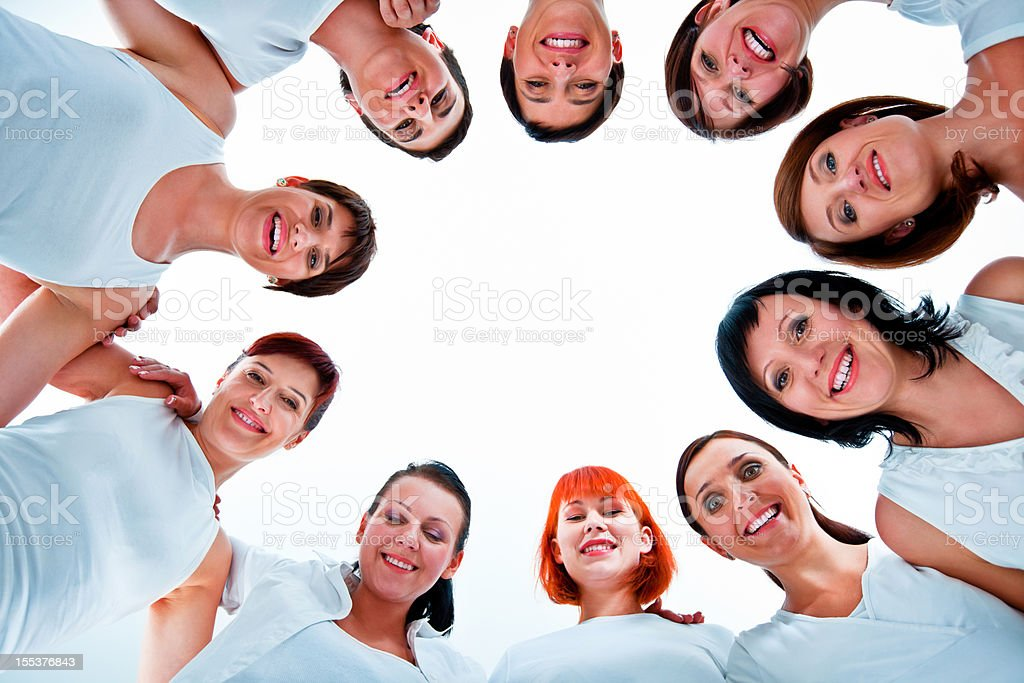 Togetherness Group of women standing in the circle, smiling at the camera against white background. Low angle view. Adult Stock Photo
