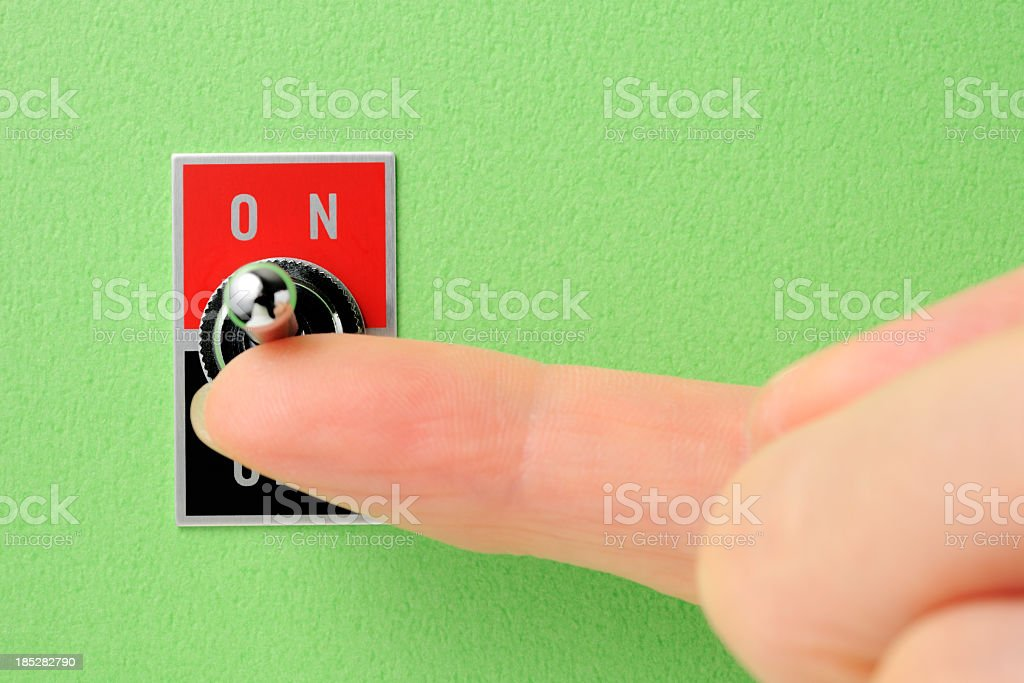 Toggle switch on green wall with index finger stock photo