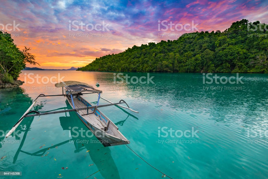Togian Islands Indonesia sunset over caribbean sea, dramatic sky, traditional boat floating on blue green lagoon in the Togean Islands, Sulawesi, travel destination in Indonesia. stock photo