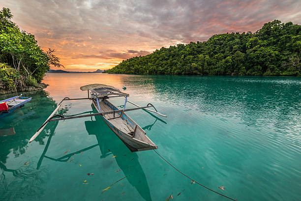 Togian Islands Breathtaking colorful sunset and traditional boat floating on blue lagoon in the Togean (or Togian) Islands, Central Sulawesi, Indonesia. sulawesi stock pictures, royalty-free photos & images