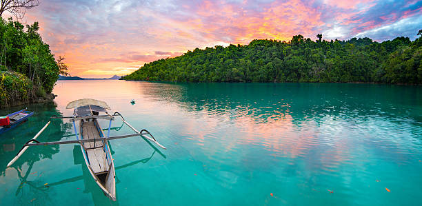 Togian Islands travel destination Breathtaking colorful sunset and traditional boat floating on scenic blue lagoon in the Togean (or Togian) Islands, Central Sulawesi, Indonesia, upgrowing travel destination. sulawesi stock pictures, royalty-free photos & images