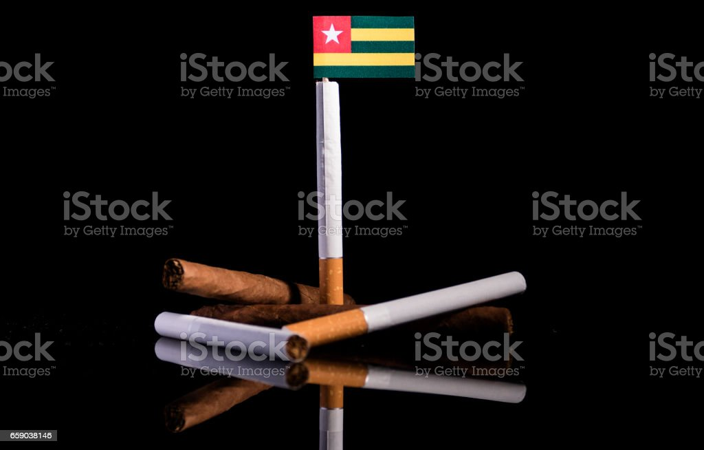 Togolese flag with cigarettes and cigars. Tobacco Industry concept. royalty-free stock photo