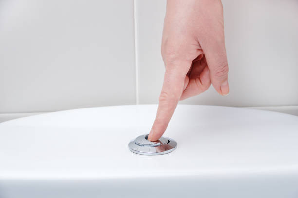 toilet bowl Hand pushing a button to flush a close tool flushing water stock pictures, royalty-free photos & images