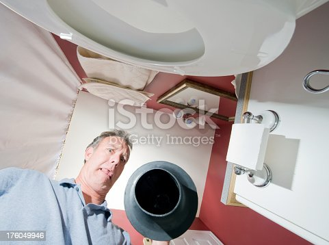 A man uses a plunger on a plugged toilet.