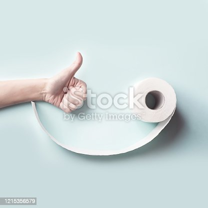 istock Toilet paper and hand. Form a face with a smile. A concept on the theme of coronavirus 1215356579
