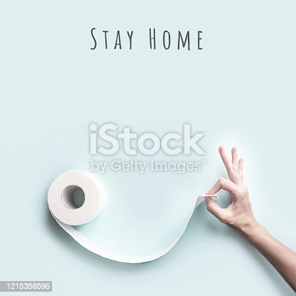 istock Toilet paper and hand with a gesture ok. Form a face with a smile. A concept on the theme of coronavirus 1215356595