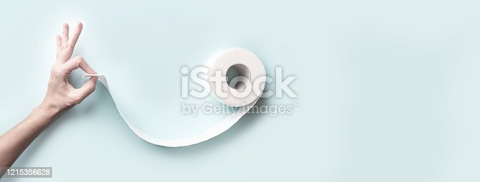 istock Toilet paper and hand with a gesture ok. Form a face with a smile. A concept on the theme of coronavirus 1215356628