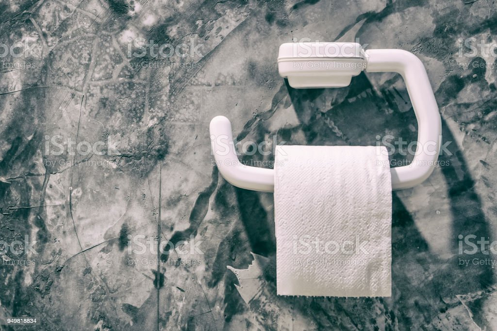 Toilet paper roll in restroom.Paper roll with cement wall bathroom background.Diarrhea concept stock photo