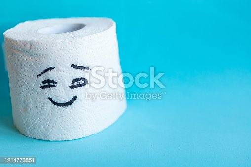 istock Toilet paper with a picture of a smiling face on blue background 1214773851