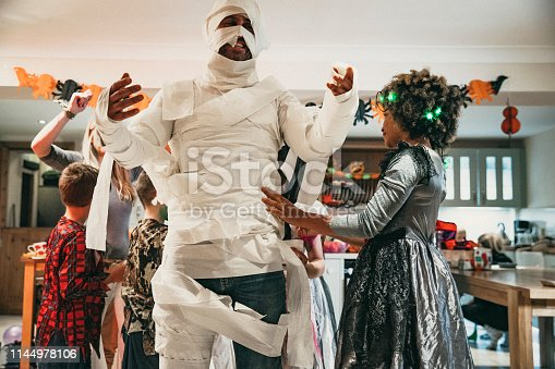 Group of children dressing one of their parents in toilet roll to look like a mummy while at a Halloween party.