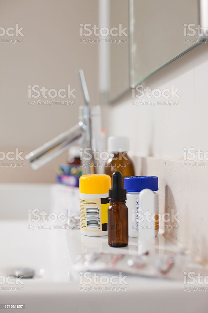 Toiletries and medication on sink in bathroom stock photo