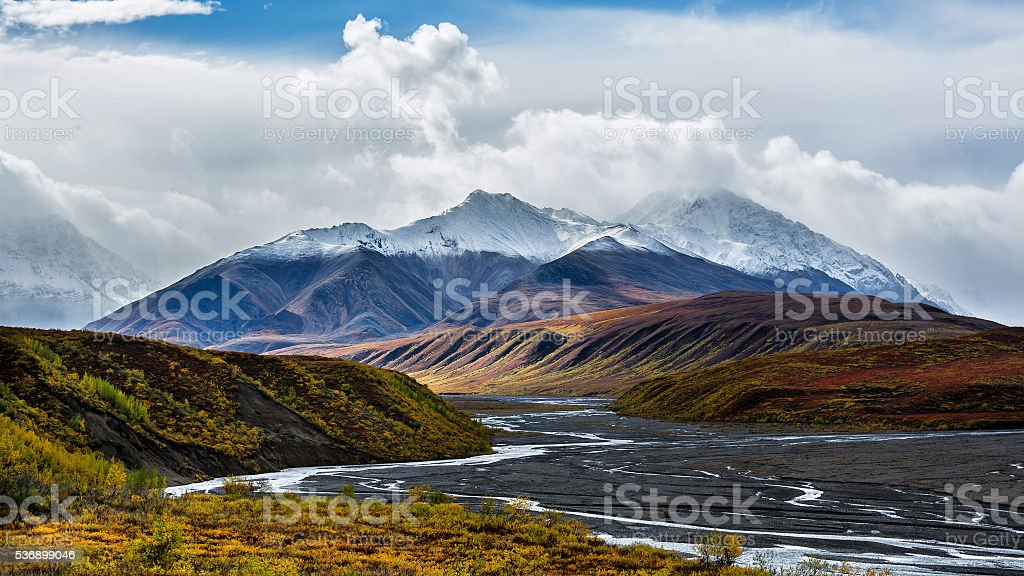 Toklat river with Autumn foliage and snow-capped mountains stock photo