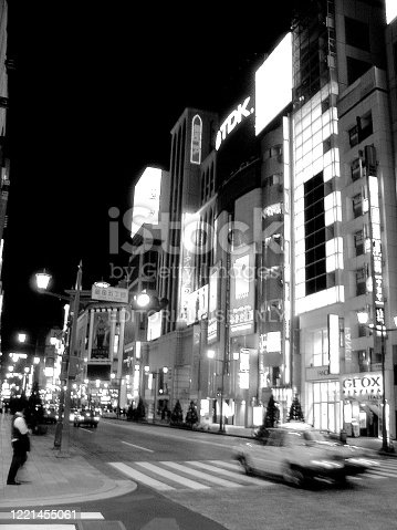 Tokyo is a major international city that is known for mixing ultra-modern with traditional.  It is also Japan's capital, which in 2019 had an estimated population of 13.9 million.   This vertical photograph, shot in September of 2007, shows a Tokyo street during nighttime.  There's also a person (towards the left side of the image) who is waiting to cross the road, while a vehicle (in blurred motion) is passing by.  A few examples of modern Japanese architecture are also present in this photograph.