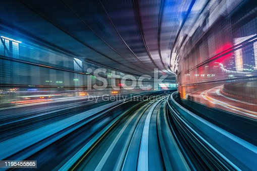High speed train driving along the rails through a train station tunnel at night. Motion Blur. Long Exposure. Edited, Composite Night Skyline. Odaiba, Tokyo, Japan, Asia
