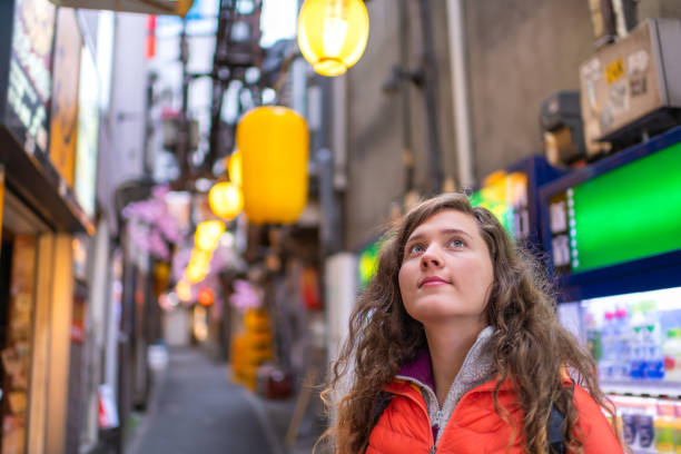 Tokyo, Japan Memory lane piss alley with yellow paper lamps lanterns bokeh background and young foreigner woman in Shinjuku area of city stock photo