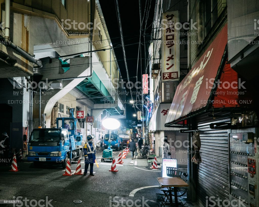 A man wearing a uniform stands at the entrance to a construction area...