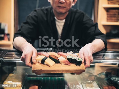 A sushi chef working in a small shop in Tokyo, Japan.