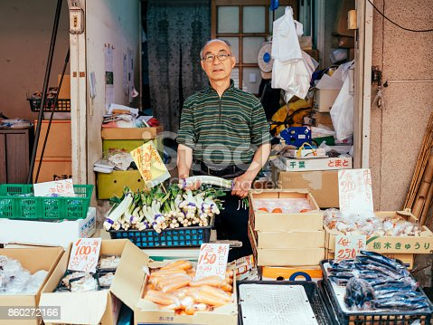 A shop owner working in his vegetable stand in Tokyo, Japan.