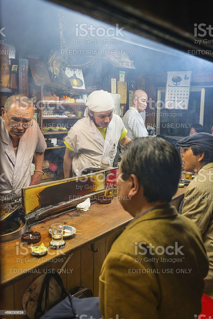 Tokyo locals and cooks in traditional smokey bar restaurant Japan royalty-free stock photo