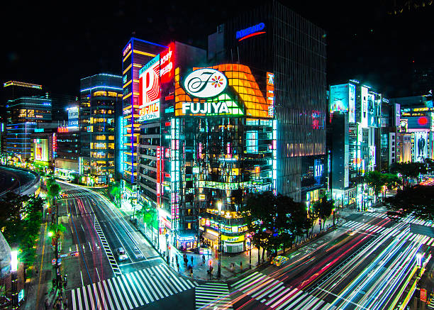 Tokyo Night Taken November 2016 - Intersection in Ginza, Tokyo illuminating the evening streets. electronic billboard stock pictures, royalty-free photos & images