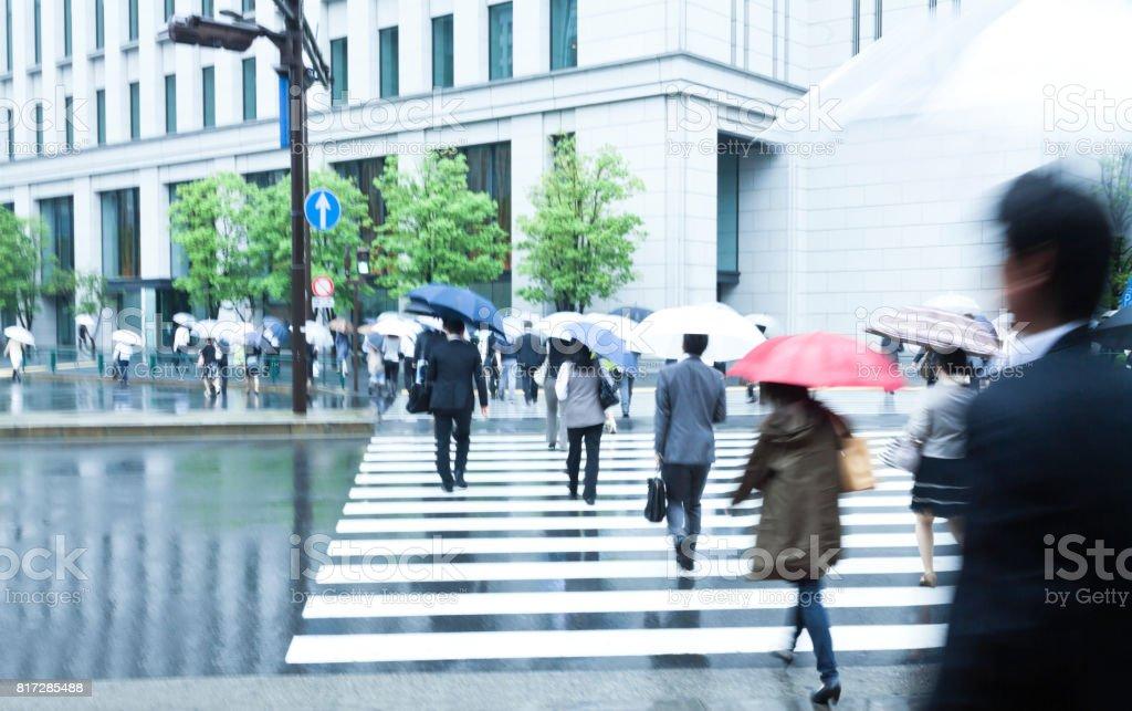crowds of tokyo city commuters walking through pedestrian walkway...
