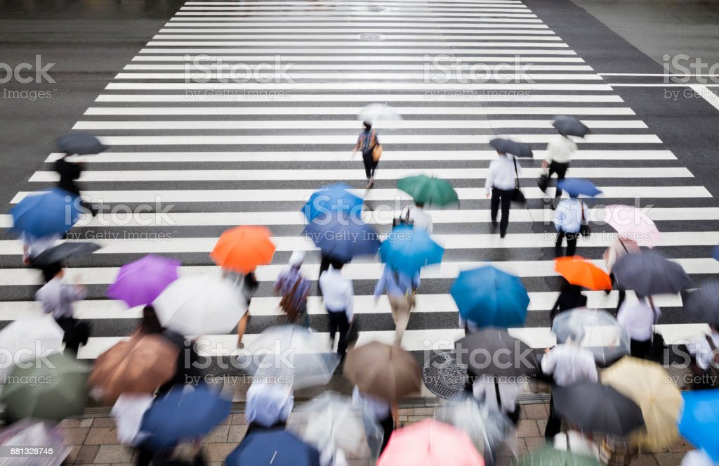 city commuters at crosswalk on a rainy morning