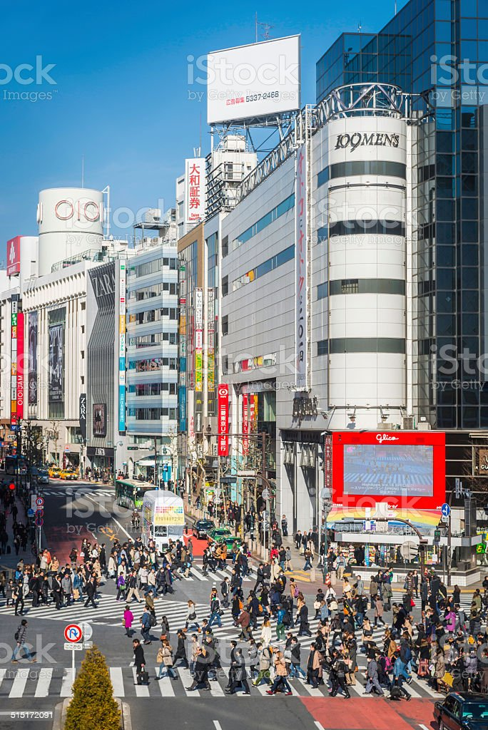 Crowds rushing across the busy junction of Shibuya Crossing, the...
