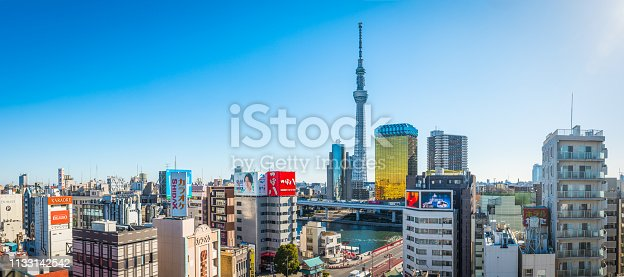 The iconic spire of the Tokyo Skytree overlooking the highrise cityscape of the Sumida River waterfront on a clear morning in the heart of central Tokyo, Japan's vibrant capital city.