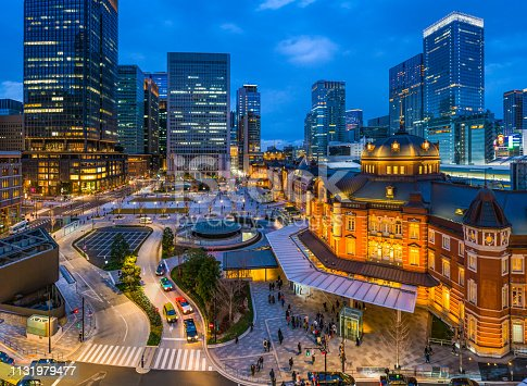 High angle view over the busy Marunouchi entrance to Tokyo Station at dusk, overlooked by the crowded skyscraper cityscape of central Tokyo, Japan's vibrant capital city.