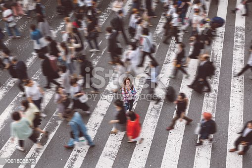 Tourist woman in Tokyo standing at zebra crossing and looking up to the camera
