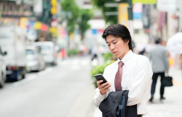 東京の青年実業家のスマート フォンを使用して ストックフォト