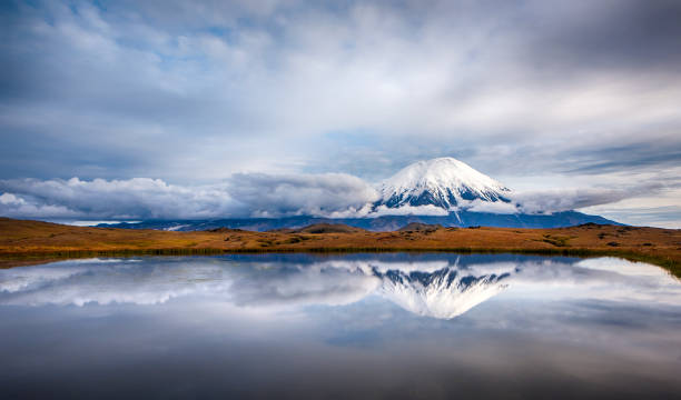 Tolbachik volcano on the Kamchatka Peninsula, Russia Tolbachik volcano (3.682 m) with reflection in a small lake. Tolbachik is one of the most active volcanoes on the Kamchatka Peninsula, Russia. The last massive eruption was in 2013. kamchatka peninsula stock pictures, royalty-free photos & images