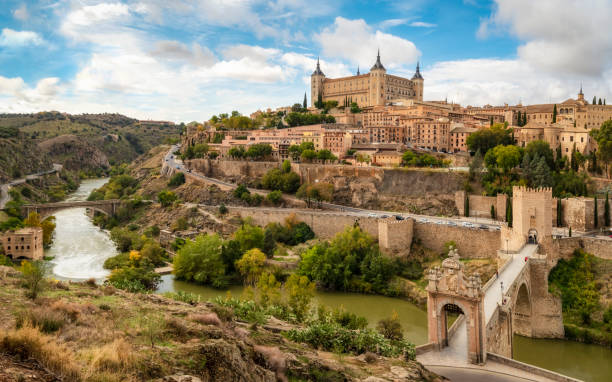 Toledo view from alcantara bridge, Spain Toledo cityscape with Alcantara bridge (Puente de Alcantara) over Targus river. Spain iberian stock pictures, royalty-free photos & images