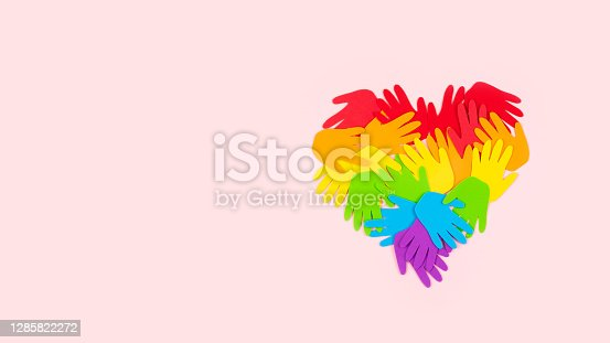 Tolerance, kindness, cooperative, friendship, charity humanitarian aid day concept. Many rainbow color palm hands on pink background with copy space.