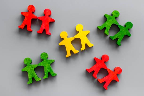 toleranz, sozialschutz, antidiskriminierungskonzept. hölzerne menschliche figuren auf grauem tisch, ansicht von oben - antidiscrimination stock-fotos und bilder