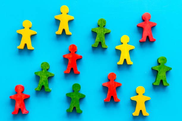 toleranz, sozialschutz, antidiskriminierungskonzept. hölzerne menschliche figuren auf blauem tisch, ansicht von oben - antidiscrimination stock-fotos und bilder