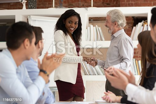 Best employee concept, proud tolerant old senior manager boss handshaking promoting rewarding happy african black young woman office worker, team applauding, recognition acknowledgement at work