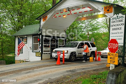 Dingmans Ferry, NJ USA May 4 2009 A car stops at a toll booth on the Dingman Ferry Bridge in New Jersey.  The bridge is one of the few remaining privately owned toll bridges in the United States