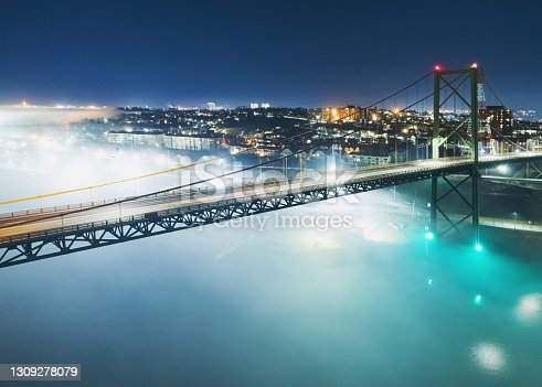 A night time aerial drone view of the MacKay bridge spanning Halifax harbour. A fog bank enshrouds the area.