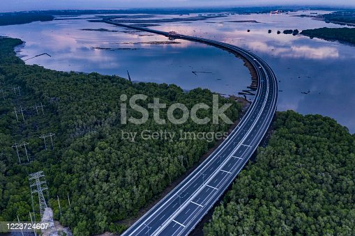 Aerial morning view of the main tollway road cutting through a bay in Bali Indonesia