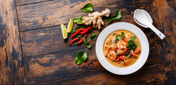 Tom Yam kung Spicy Thai soup Tom Yam kung Spicy Thai soup with shrimp, seafood, coconut milk and chili pepper in bowl on wooden background copy space asian food stock pictures, royalty-free photos & images