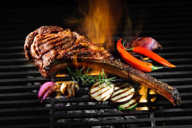 tomahawk rib biefstuk op grill - ribeye biefstuk stockfoto's en -beelden