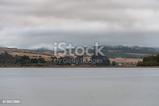 Tomales Bay with view of rolling hills on a cloudy day with fog.