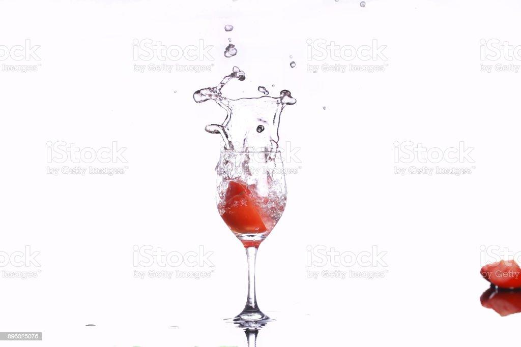 tomateos spashing into wine glass stock photo