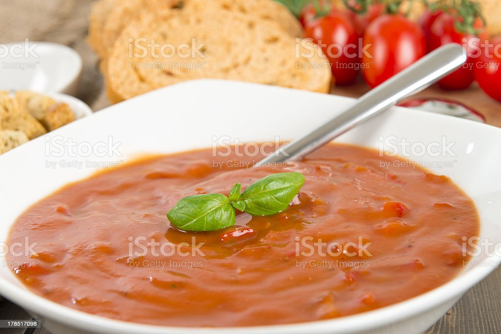\'Chunky tomato and red pepper soup garnished with basil leaves, with...