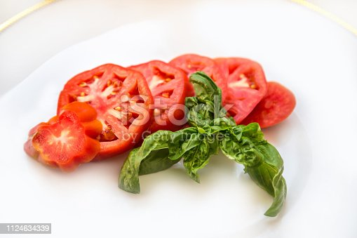 Sliced tomato with a basil leaf on a white plate